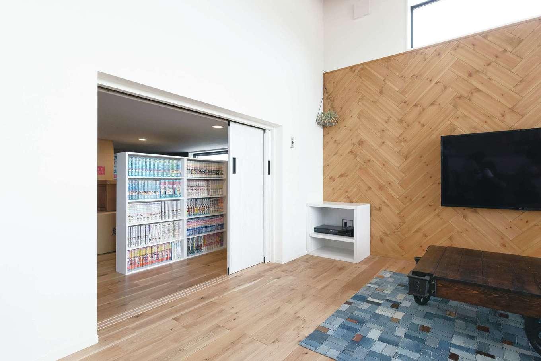小玉建設【デザイン住宅、間取り、スキップフロア】スキップフロアの下を利用して、リビングの隣に7.5畳の納戸を確保。「ロフトだと荷物の出し入れが大変ですが、これなら両親も使いやすいと思って」とご主人。出入口が2か所あり、ご両親の荷物は廊下側から出し入れできるので便利。書棚も設けてあり、ライブラリーとしても活躍