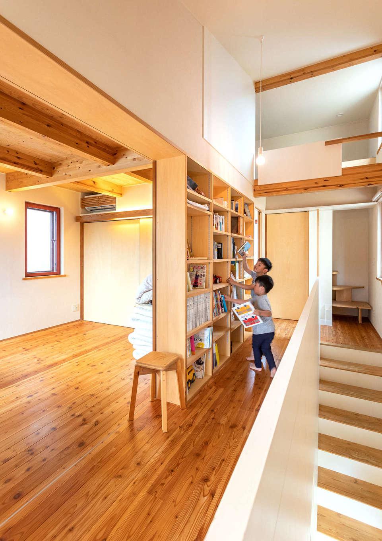 入政建築【子育て、狭小住宅、間取り】2階も仕切りのないオープンな間取り。寝室の壁の裏面を書棚に利用して空間を無駄なく利用。階段の正面奥には、小屋裏に繋がる階段がある