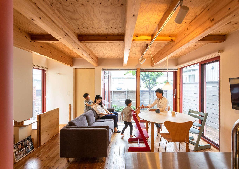 入政建築【子育て、狭小住宅、間取り】無垢の床と珪藻土の壁が素朴な心地よさをもたらすLDK。シンプル&ナチュラルな空間に、木製サッシの赤が映える。光や風を暮らしに活かすパッシブデザインと、太陽熱で室内を暖める「びおソーラー」を採用し、春と秋の「中間期」を延長した暮らしが実現