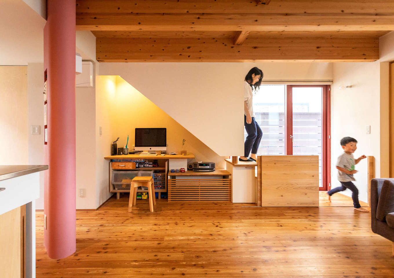 入政建築【子育て、狭小住宅、間取り】階段下のデッドスペースにはカウンターと造作家具を設けて書斎や勉強コーナーとして利用。室内の三方向に掃出窓とウッドデッキを設けたことで、床が外に広がるような視覚的効果をもたらし、いっそう開放的に感じられる