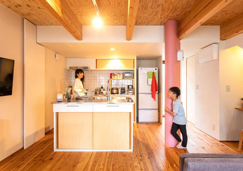 入政建築【子育て、狭小住宅、間取り】I列+アイランド型の造作キッチン。アイランド側にはシンクがあり、家族みんなで片付けや配膳ができる。キッチンの隣のコーラルピンクの柱は、構造部分の柱と「びおソーラー」のダクトを囲って意匠的に造作したもの。柱の裏側に住設関連の操作パネルをまとめたニッチも設けてある