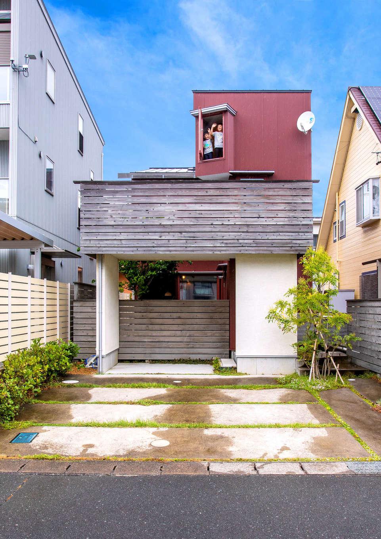 入政建築【子育て、狭小住宅、間取り】閑静な住宅街に建つ2階建ての外観。約39坪の敷地内に2台分の駐車スペースと庭も確保。駐車場と玄関ポーチと塀の奥に庭を設けて周囲の視線を遠ざけ、プライバシーに配慮。おかげで室内の掃出窓を開け放って過ごすことができ、庭でも気兼ねなくくつろげる