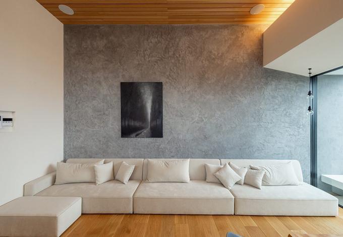 HAPINICE -ハピナイス-【豊橋市東幸町・モデルハウス】リビングで目を惹く美しい壁。天然石のような風合いは上質な空間を作り上げる