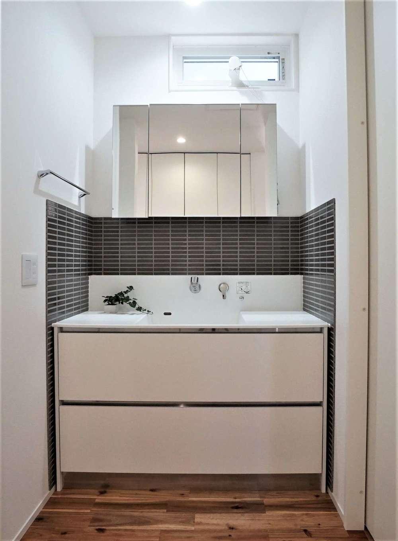 RIKYU (リキュー)【デザイン住宅、間取り、建築家】タイルがモダンな印象を与えるサンワカンパニーの洗面台。洗面室と脱衣室を分けたことで、誰かが入浴中でも歯磨きや洗面ができる