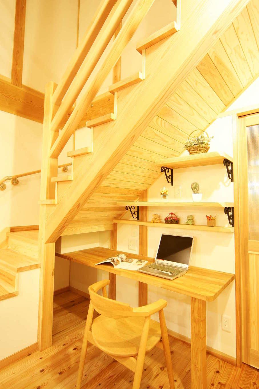 住まいるコーポレーション【収納力、和風、自然素材】大工さんの見事な職人技が光る階段。その下のスペースを有効活用して、奥さまの書斎兼家事コーナーを作った。アイアンの棚受け金具もポイント