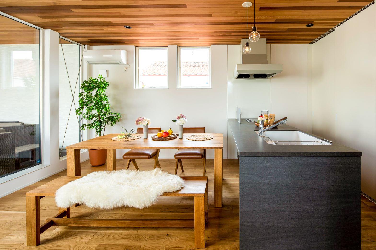スタイルカーサ【浜松市中区飯田町・モデルハウス】2階のダイニングキッチン。床は無垢オーク材、天井はレッドシダーを貼り、木のぬくもりを感じる。シンプルで洗練されたデザインのキッチンはTOCLAS製。白い引き戸でバックヤードの食器や調理家電を隠せるので生活感が出ない