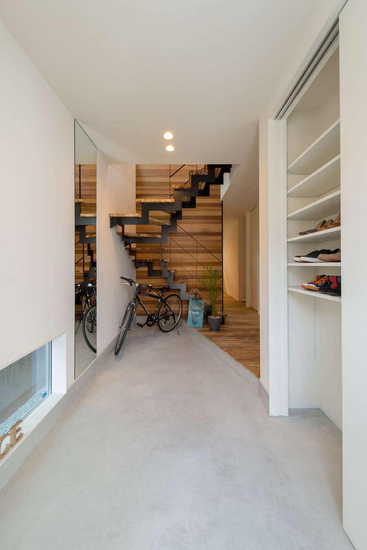 HAPINICE -ハピナイス-【デザイン住宅、間取り、平屋】土間を広く設けた玄関。地窓で明るさを確保し、収納も充分に設けてある。奥の階段を上がると、その先にはリゾートチックなLDKが広がる