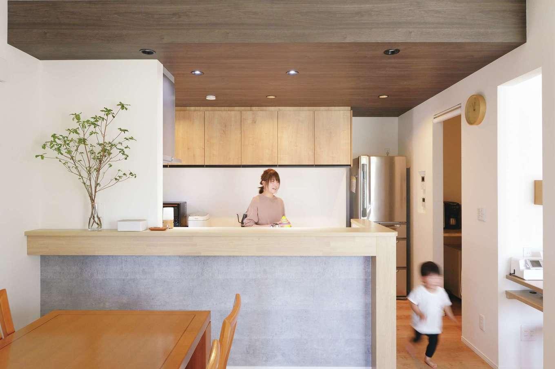 丸昇彦坂建設【デザイン住宅、子育て、間取り】対面キッチンは腰壁を高めに設定し、作業の手元がダイニングから見えないように配慮されている。腰壁のグレーとカウンターのベージュ、天井の茶色のカラーコーディネートが絶妙にマッチ