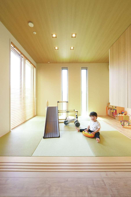 丸昇彦坂建設【デザイン住宅、子育て、間取り】奥さまの両親が泊まりに来ることも考えて、LDKに続き間の和室を配置。3方向に窓を設け、明るく開放的な空間に。現在はキッズコーナーとして活躍し、地窓の上の吊戸棚にはおもちゃをたっぷり収納。デッキにも直接出入りでき、子どもがのびのびと遊ぶことができる