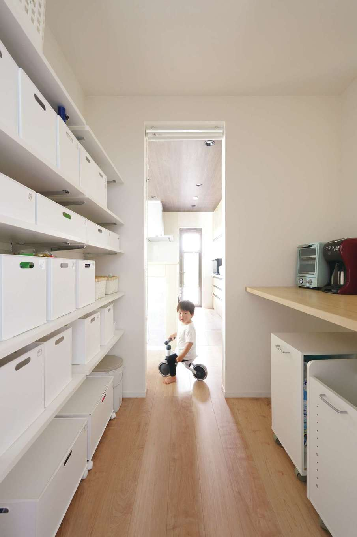 丸昇彦坂建設【デザイン住宅、子育て、間取り】キッチンの横にある家事カウンター付のパントリー。浴室と繋がっていて、玄関にも通り抜けができる
