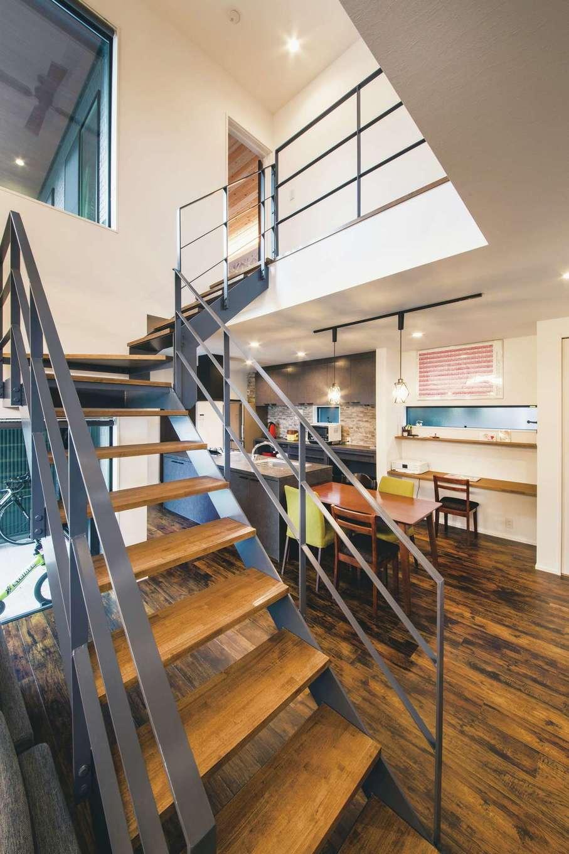 内田建設【デザイン住宅、狭小住宅、建築家】夫婦の夢だったアイアンのオープン階段。家の中央にレイアウトしたことで、リビングとダイニングキッチンがさり気なくエリア分けされるようになった。1階にいても、吹抜けを通して2階の音が聞こえるので子育てママも安心♪