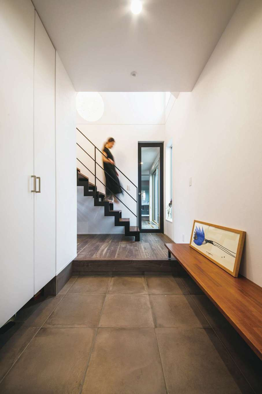 コットンハウス【デザイン住宅、省エネ、間取り】玄関の正面にアイアンのスケルトン階段を配し、シンプルな空間をスタイリッシュに演出。正面のドアの先にLDKがある