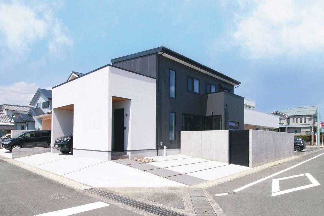 コットンハウス【デザイン住宅、省エネ、間取り】白い塗り壁とグレーのガルバリウム鋼板の外壁を組み合わせた外観。周囲をフェンスで囲み、プライベート感あふれる庭を実現
