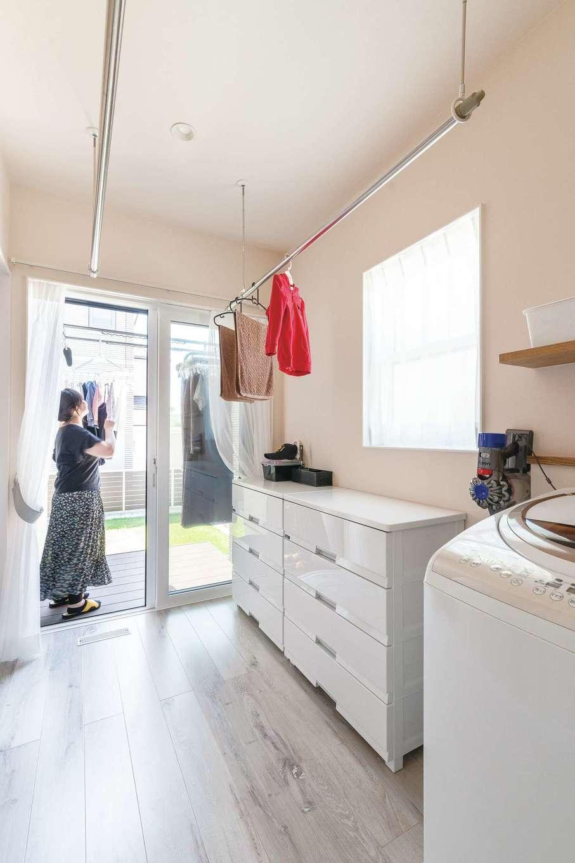 四季彩ひだまり工房 高田工務店【子育て、収納力、間取り】洗濯機と収納を備えるユーティリティを、キッチン裏に配置。平日夜の室内干しスペースとしても十分な広さを確保。休日は外に干すため、ウッドデッキを連結した