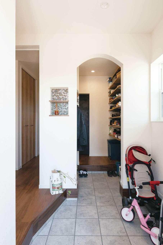 四季彩ひだまり工房 高田工務店【子育て、収納力、間取り】ベビーカーを置いても広々とした玄関。シューズクロークへ続くアール型の垂れ壁がかわいい。奥に見える黒いドアは、ご主人の書斎