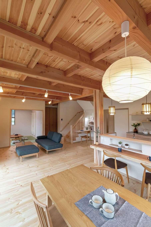 住まいるコーポレーション【デザイン住宅、和風、自然素材】天然木と珪藻土が家族の暮らしをやさしく包み込むLDK。床は30mmもの厚さのパイン材を使用。天井も厚さ12mmのパインの板張りで、ダイナミックな梁組みが印象的