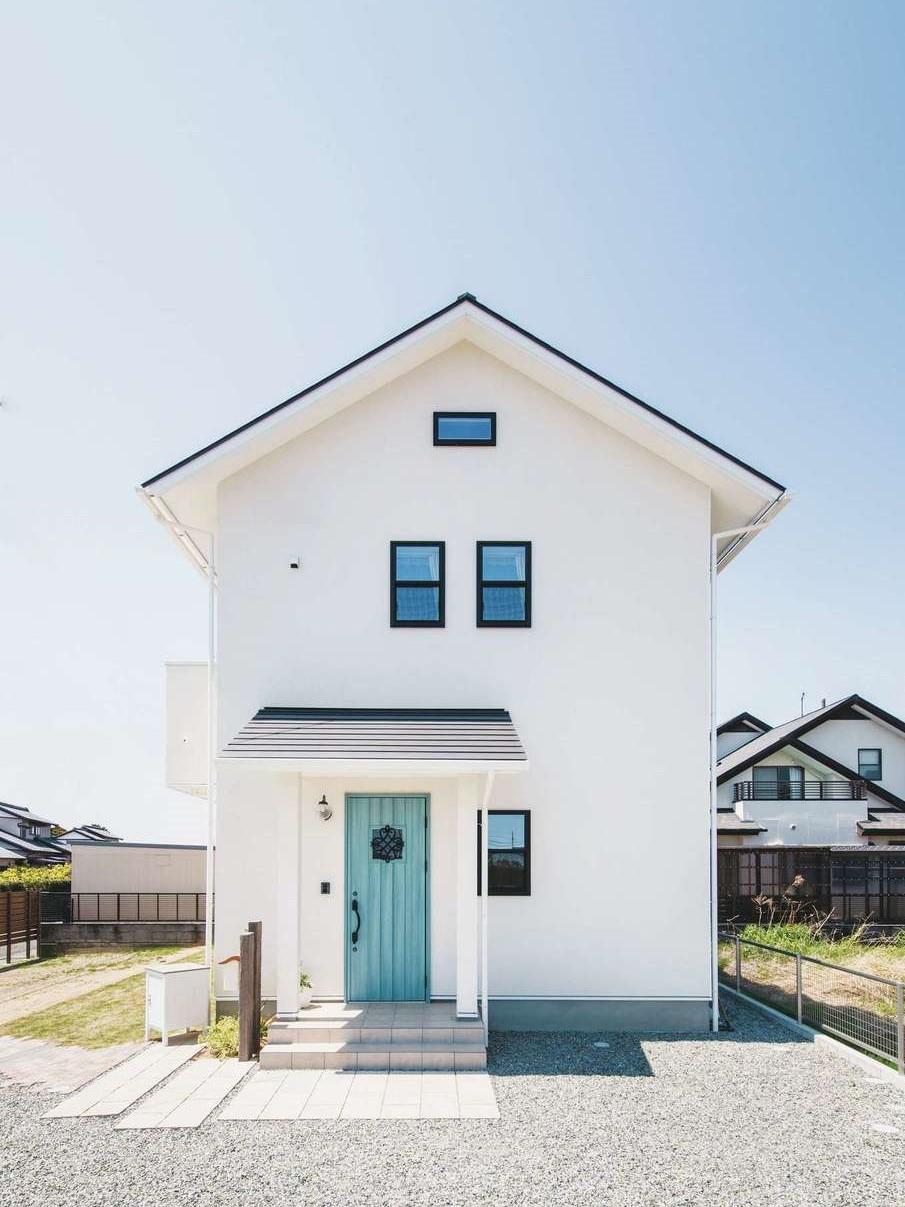 ワンズホーム【デザイン住宅、子育て、間取り】真っ白な塗り壁に青い玄関ドアが映え、まさにカフェのよう。サッシや屋根を黒にすることで、白がより美しく輝く