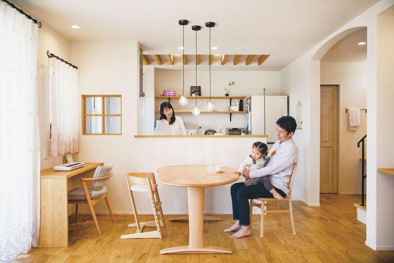 ワンズホーム【デザイン住宅、子育て、間取り】無垢フローリングの優しい色合い、キッチンの小窓、アール型開口などがかわいらしい印象をもたらすLDK。将来子どものスタディコーナーに使う予定の造作カウンターは、テレワーク導入が始まったご主人の書斎としても活躍しているそう。奥さまがこだわって選んだレースのカーテン、ダイニングテーブル上部のペンダント照明が空間に華を添え、カフェのような雰囲気にホッと心が和む