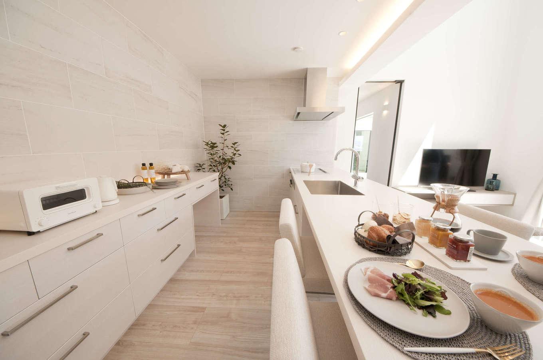 レオック【豊橋市神野新田町中島10・モデルハウス】「Works」2階キッチン。ダイニングテーブルとキッチンが一体化したデザインは、配膳・片付けの動作が効率的に。背面収納とパントリー収納を設け、気になるキッチンまわりをスッキリ見せる