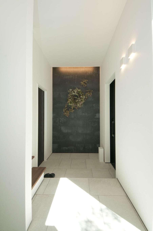 レオック【豊橋市神野新田町中島10・モデルハウス】「Court」1階ダークグレーのタイルがアクセントの玄関。玄関土間と一続きになった玄関収納を設け、生活感をなくしたスタイリッシュな空間に