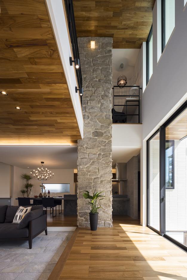 幸和ハウジング【静岡市駿河区桃園町1-1・モデルハウス】天然石を張った壁が吹抜けを貫くかのように存在感を放つLDK。南北の両側に庭と大開口を設けてある。縦横に広がりのある空間でありながら、高断熱の構造とパッシブデザインにより、室内全体が年中快適。冬は床暖房のみで暖かく過ごすことができる