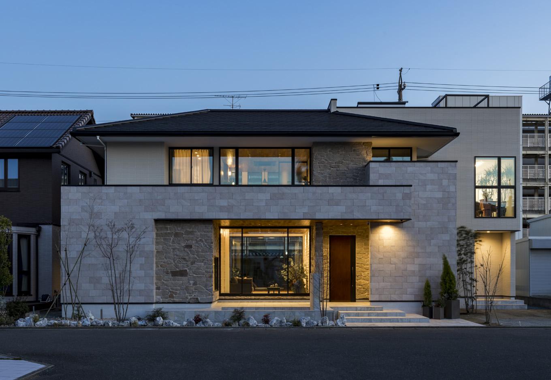 幸和ハウジング【静岡市駿河区桃園町1-1・モデルハウス】薄暮に包まれた外観。洗練されたフォルムに、灯りがやさしい表情をもたらしている。深い軒の下はテラスとして利用。水盤も設けてあり、リゾート気分を味わえる