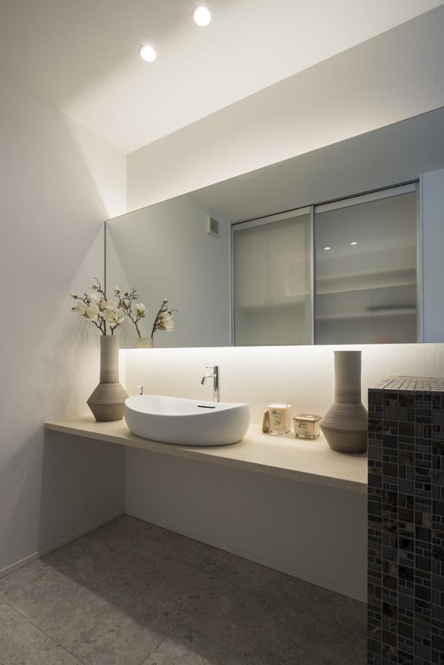 幸和ハウジング【静岡市駿河区桃園町1-1・モデルハウス】ホテルライクなデザインが奥さまに人気の洗面スペース。鏡に映っているのは、背面の収納スペース。家族分の着替えや洗剤などのストック品をたっぷり収納できる