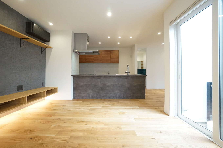 RIKYU (リキュー)【収納力、間取り、建築家】19畳のLDK。中庭から燦々と光が降り注ぎ、明るくて開放的な空間を実現。テレビステーションはキッチンの素材、色に合わせてモルタル風仕上げに。床は無垢のオーク材で、一年中素足で過ごしたくなるほど気持ちいい