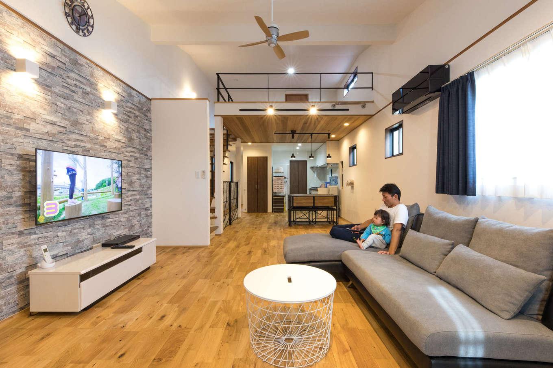 建築システム(狭小住宅専門店)【1000万円台、狭小住宅、ガレージ】2階のワンフロアは、大きなロフトのあるLDKに。勾配天井を活かして、リビング部分は縦方向の開放感も演出。テレビボード側の壁にはストーン柄のアクセントクロスを用いてシックな印象に