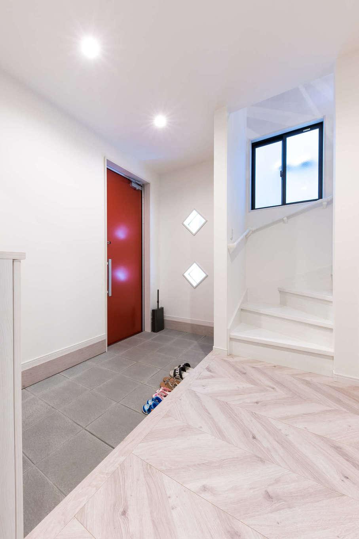 建築システム(狭小住宅専門店)【1000万円台、狭小住宅、ガレージ】白を基調にした明るい玄関ホール。赤い玄関ドアがアクセントに。1階は居室も白基調で統一している