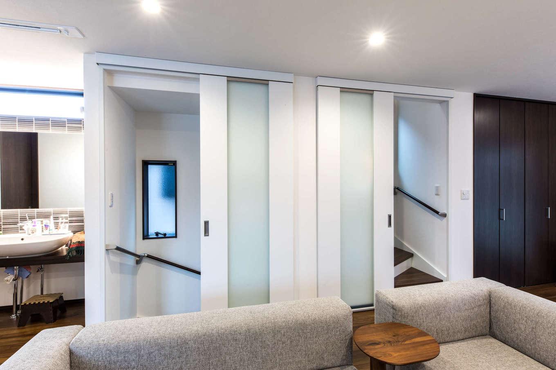 建築システム(狭小住宅専門店)【収納力、二世帯住宅、狭小住宅】階段は家の中央に配して、家族の上り下りの際に必ずリビングを通る動線に。スペースが節約できる引き戸を取り付け、各階の冷暖房効率に配慮している