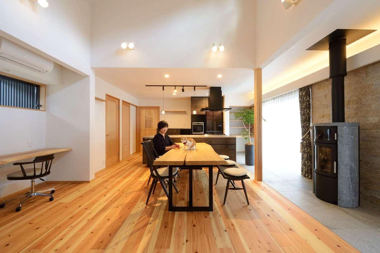 ツリーズ【趣味、自然素材、平屋】開放感あふれるナチュラルテイストのLDK。肌ざわりのいい無垢の床は厚さ30ミリの杉板。土間に設置したスタイリッシュな薪ストーブがインテリアの一部にもなっている