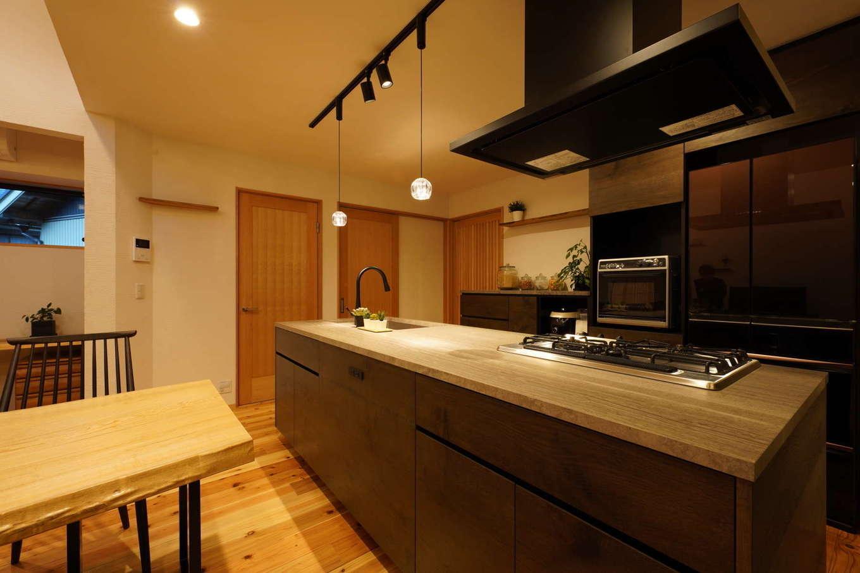 ツリーズ【趣味、自然素材、平屋】フルオーダーメイドのアイランドキッチン。天板は大理石、扉は墨を重ね塗りしてニュアンスを出している。シンプルでおしゃれなペンダントライトにも施主さんのこだわりを感じる