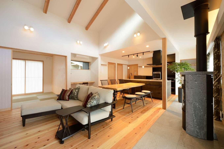 ツリーズ【趣味、自然素材、平屋】高い勾配天井に目線が抜けて、より広く感じられるLDK。天井と壁に調湿・消臭効果にすぐれた漆喰を採用し、常にきれいな空気が流れる。冬は薪ストーブ1台で家中がぽっかぽか