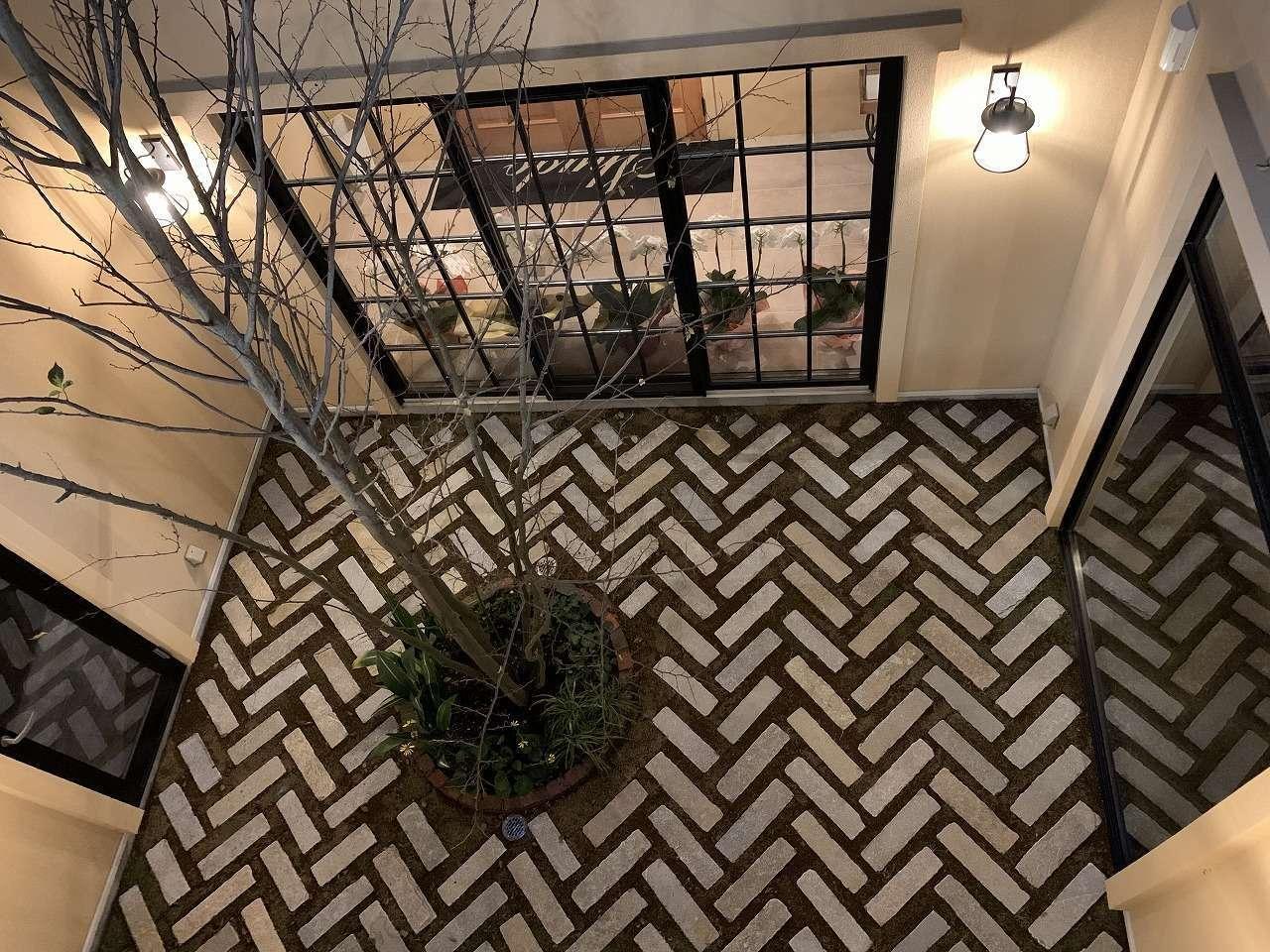 ツリーズ【デザイン住宅、輸入住宅、建築家】中庭の床はヘリンボーン張りのフロアタイル。窓の黒い格子もヨーロッパ風でテンションが上がる