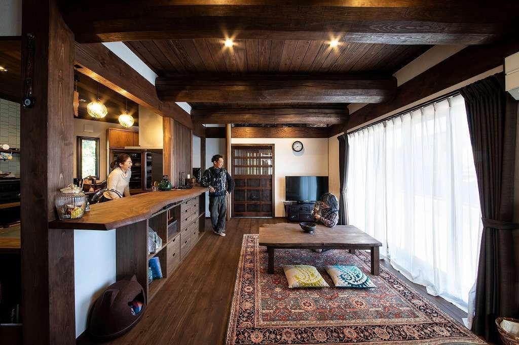 ツリーズ【自然素材、間取り、インテリア】外からは想像もつかない古民家風の室内。太い梁、無垢の床、天井、漆喰はすべて夫婦が自分たちで塗装した。アジアン風のカーペットも古民家の空間と相性がいい