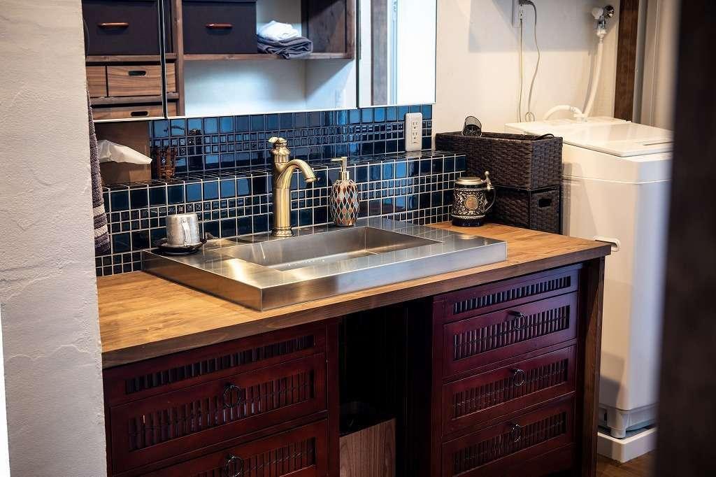 ツリーズ【自然素材、間取り、インテリア】奥さまが探してきたアンティーク調のキャビネットを使った造作の洗面台。ステンレスのシンク、ブルーのモザイクタイルとバランス良く調和している