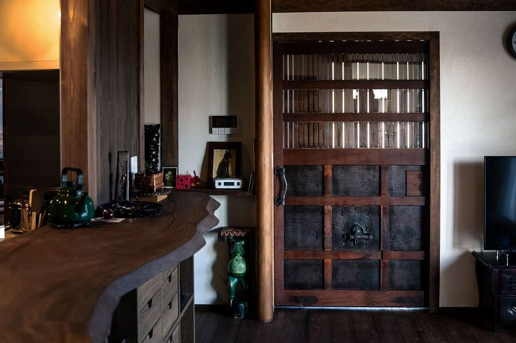 ツリーズ【自然素材、間取り、インテリア】東京の骨董店で購入した古い蔵戸をリビングドアとして使い、ニュアンスを出した。手に触れる機会が多いので、使い込むほどに味わいが出てくる