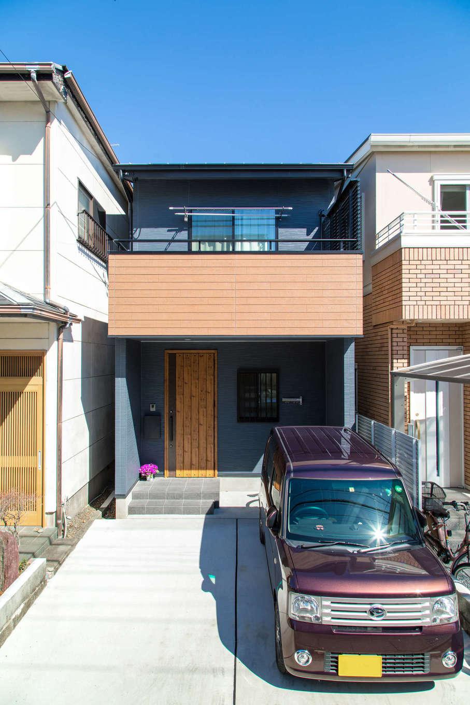 建築システム(狭小住宅専門店)【収納力、狭小住宅、夫婦で暮らす】建物の前面に2台分の駐車スペースを確保。外観はグレーと木質のサイディングでヴィンテージ調に。2階リビングに面した大きなバルコニーも希望通り