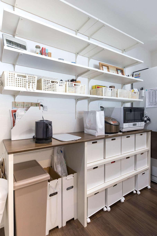 建築システム(狭小住宅専門店)【収納力、狭小住宅、夫婦で暮らす】あらかじめ置くもののサイズを測って造作したキッチンの棚。天井まで使える可動棚で収納力も抜群。すっきりと統一された収納グッズに奥さまのセンスを感じる