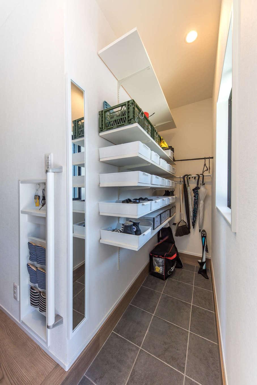 建築システム(狭小住宅専門店)【収納力、狭小住宅、夫婦で暮らす】土間収納も扉を設けずオープンスペースに。下部は将来ベビーカーを置いたり、アウトドアグッズなどの収納にも便利。ホール側にはスリッパラックも造作した