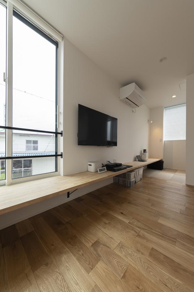 S.CONNECT(エスコネクト)【子育て、建築家、デザイン住宅】リビングに造作したカウンターは、書斎まで続いていてデスクとして使用できる。カウンターの下はAV機器や子ども用品、雑貨の収納場所として使用している