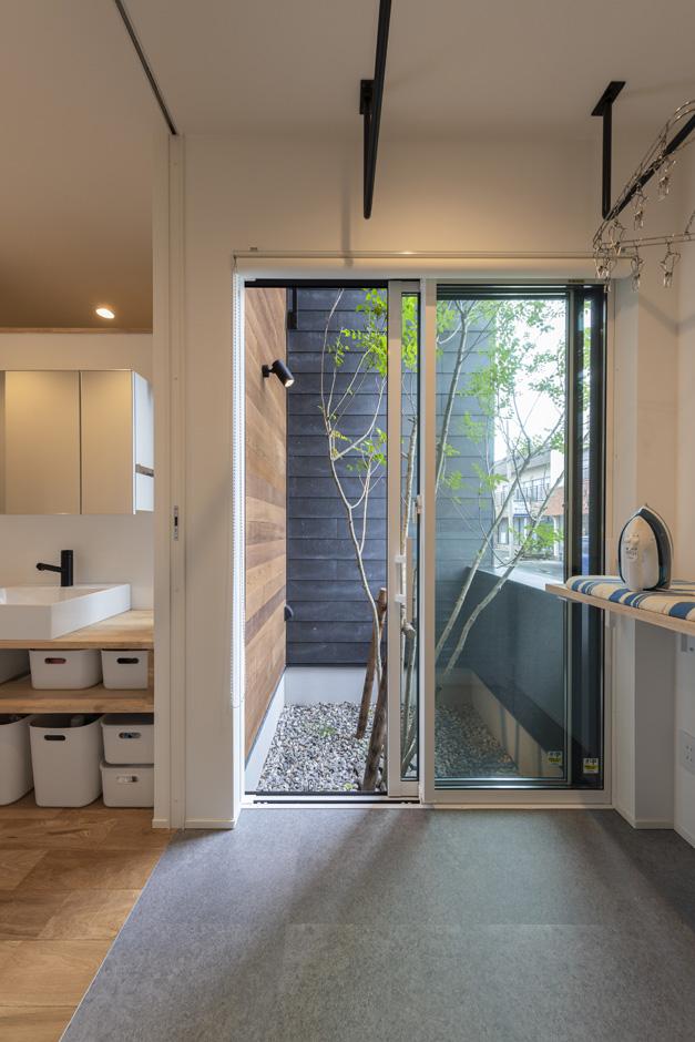 S.CONNECT(エスコネクト)【子育て、建築家、デザイン住宅】坪庭のシマトネリコを眺められる広い脱衣室には、アイロンをかけたり洗濯物を畳んだりできるカウンターを設置。左にある洗面コーナーは廊下沿いに設けてスペースを節約
