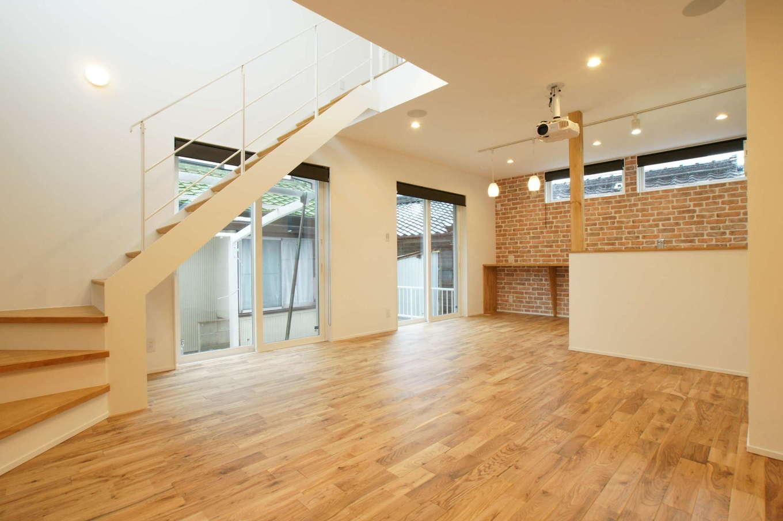 RIKYU (リキュー)【デザイン住宅、間取り、インテリア】家族の様子が見える場所にキッチンをレイアウト。バックヤードのレンガ調のクロスがアクセントに。窓も多めに設置して、十分な光と風を取り込む