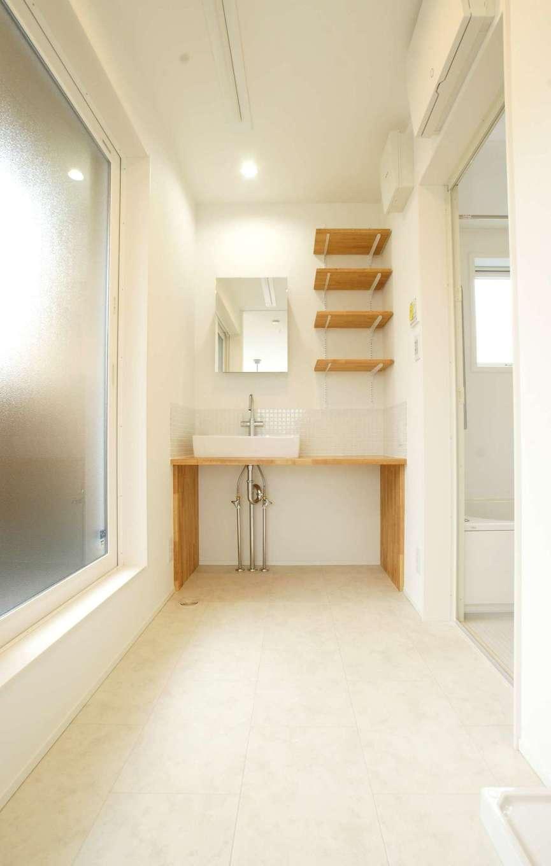 RIKYU (リキュー)【デザイン住宅、間取り、インテリア】2階の洗面脱衣室。バルコニーからの光がFIX窓から降り注ぎ、明るくて爽やかな空間を演出。カウンターと収納棚は造作