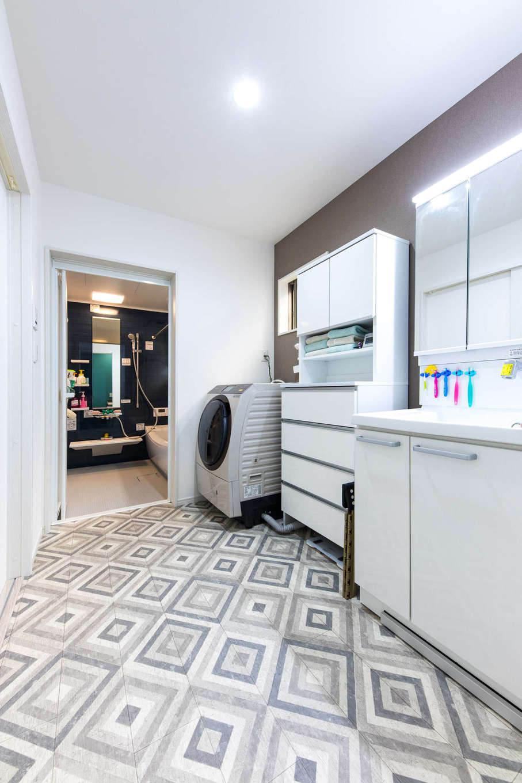 建築システム(狭小住宅専門店)【収納力、狭小住宅、間取り】洗面脱衣所は子ども3人の入浴時にもストレスがないゆとりの広さ。洗面台やチェストで収納も充実させ、タオルや洗剤などのストックもすっきり収めている