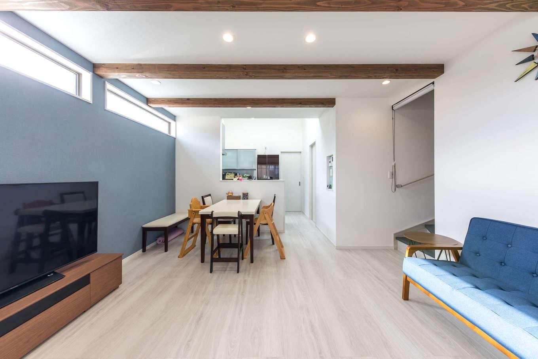 建築システム(狭小住宅専門店)【収納力、狭小住宅、間取り】見せ梁が印象的な2階に設けたLDK。空間の出っ張りをなくした設計に加え、白と木調をメインにブルーのアクセントカラーをきかせた爽やかなインテリアで広がりを感じる。西側の壁はスリット窓にして西日をカット