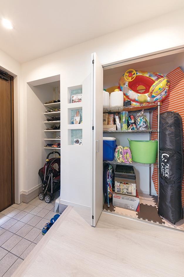 建築システム(狭小住宅専門店)【収納力、狭小住宅、間取り】玄関ホールには、階段下のスペースを活用した収納を設け、アウトドア用品の定位置に。外に物置を用意する必要が無いので、駐車スペースもゆったりしたまま。写真や小物を飾れるニッチも造作で