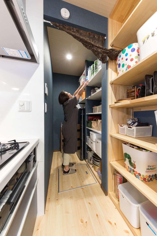 建築システム(狭小住宅専門店)【自然素材、間取り、インテリア】キッチン奥には冷凍庫も収まる大型のパントリーを完備。食材や食器のストックも万全で大勢の来客時も安心。キッチンと同じアクセントクロスで統一感をもたせた