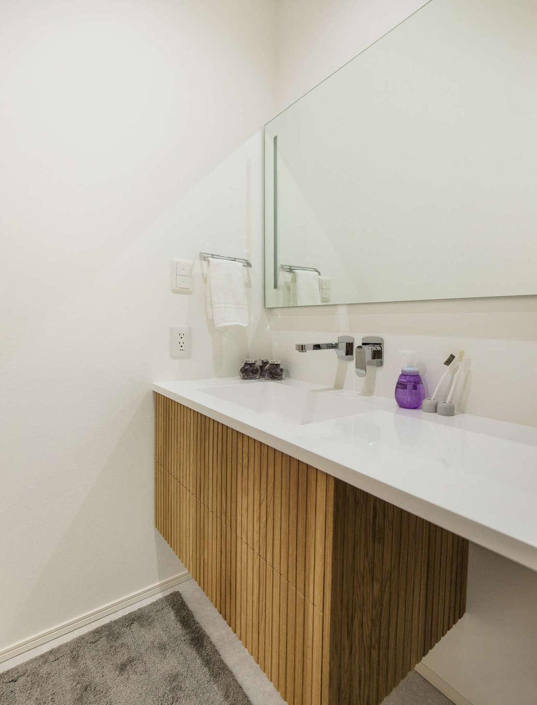 納得住宅工房【藤枝市前島3丁目12-43・モデルハウス】シンプルな中にも洗練されたデザインが光る洗面台は、同社オリジナルの「ルシェーロ」。ワイドな鏡、木目調の収納扉とバランス良く調和している